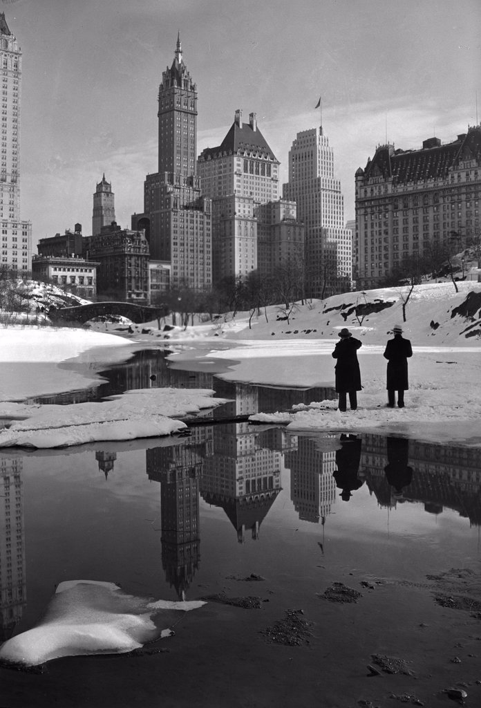 New York City, plaza buildings reflected over park lake, photograph by Samuel H. Gottscho, February 12, 1933. : Stock Photo