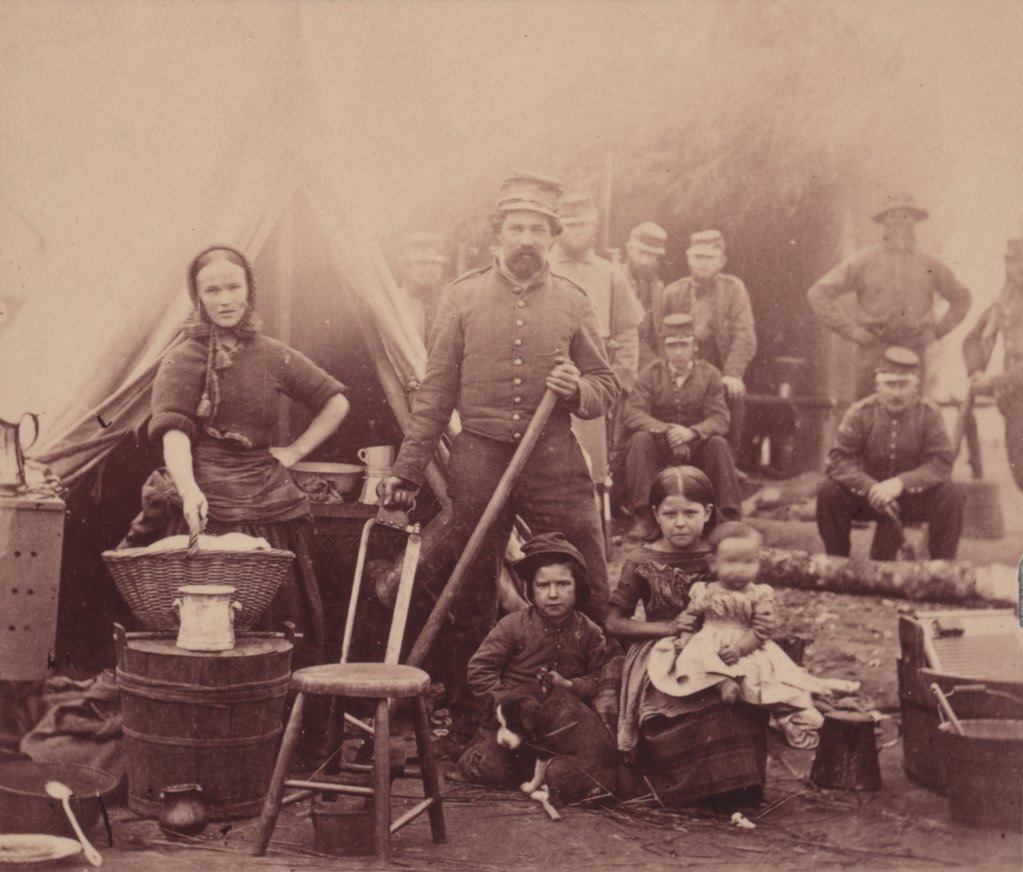 Stock Photo: 4048-4087 The Civil War, woman with sleeves rolled up holding basket, in front of tent with a soldier (possibly her husband) and three children, other soldiers in the background, camp of 31st Pennsylvania Infantry near Washington, DC, photograph, February, 1862.
