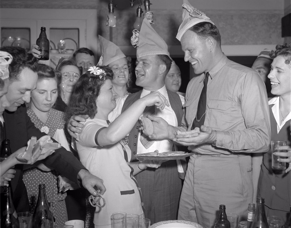World War II, George Woolslayer (center), soldier and sailor with a party at his home, friends, relatives and fellow workers made up the list of guests, Mrs. Woolslayer (left of center) helps Chief Evans (right), to a sandwich, Pittsburgh, Pennsylvania, photograph by Alfred T. Palmer, August, 1942 : Stock Photo