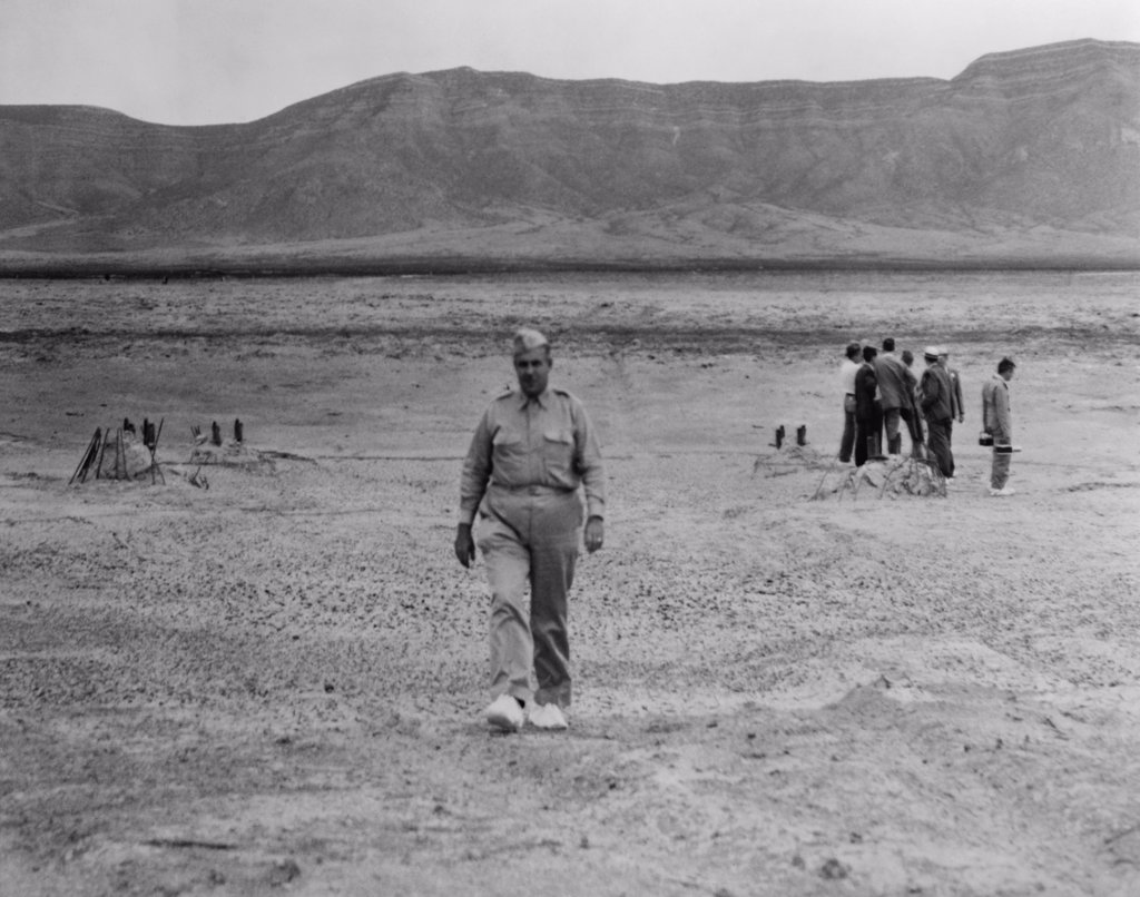 Stock Photo: 4048-5738 General Leslie Groves (1896-1970), walking across the site of the first atomic bomb blast site at Alamogordo, N.M. in July 1945. Groves was the military leader of the Manhattan Project to develop the Atomic Bomb. He was played by Paul Newman in the 1989 movie, FAT MAN AND LITTLE BOY.