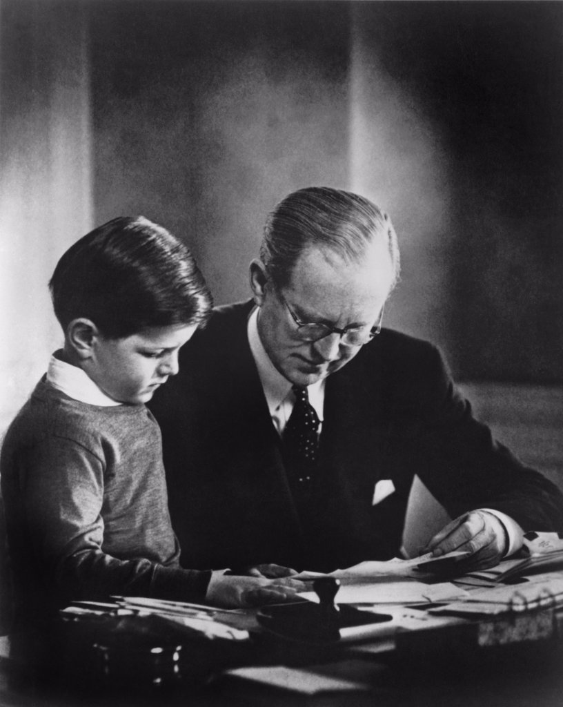 Stock Photo: 4048-5765 Ambassador to Great Britain, Joseph Kennedy, in his London study, helping his youngest son, Edward Kennedy, with his studies. Ca. 1938.
