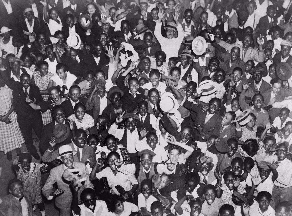 Harlem crowd celebrating African American boxer, Joe Louis' victory against former heavyweight champion, Primo Carnera. June 19, 1935. : Stock Photo