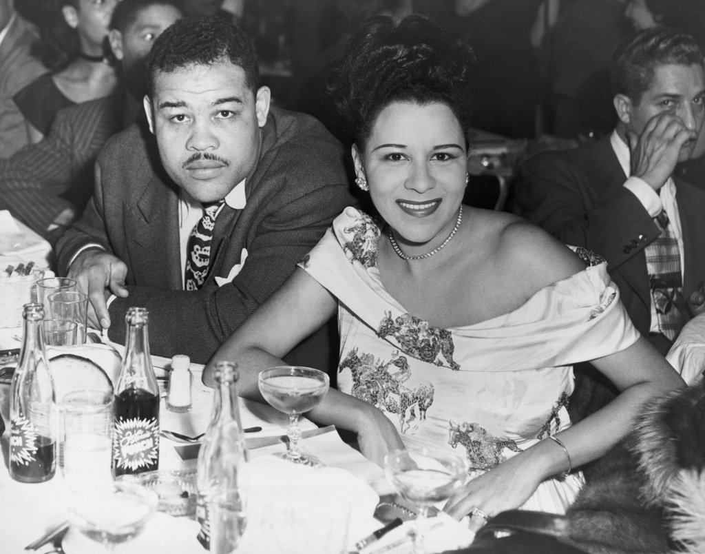 Heavyweight champ Joe Louis and his first wife Marva dining at a night club in 1947. : Stock Photo