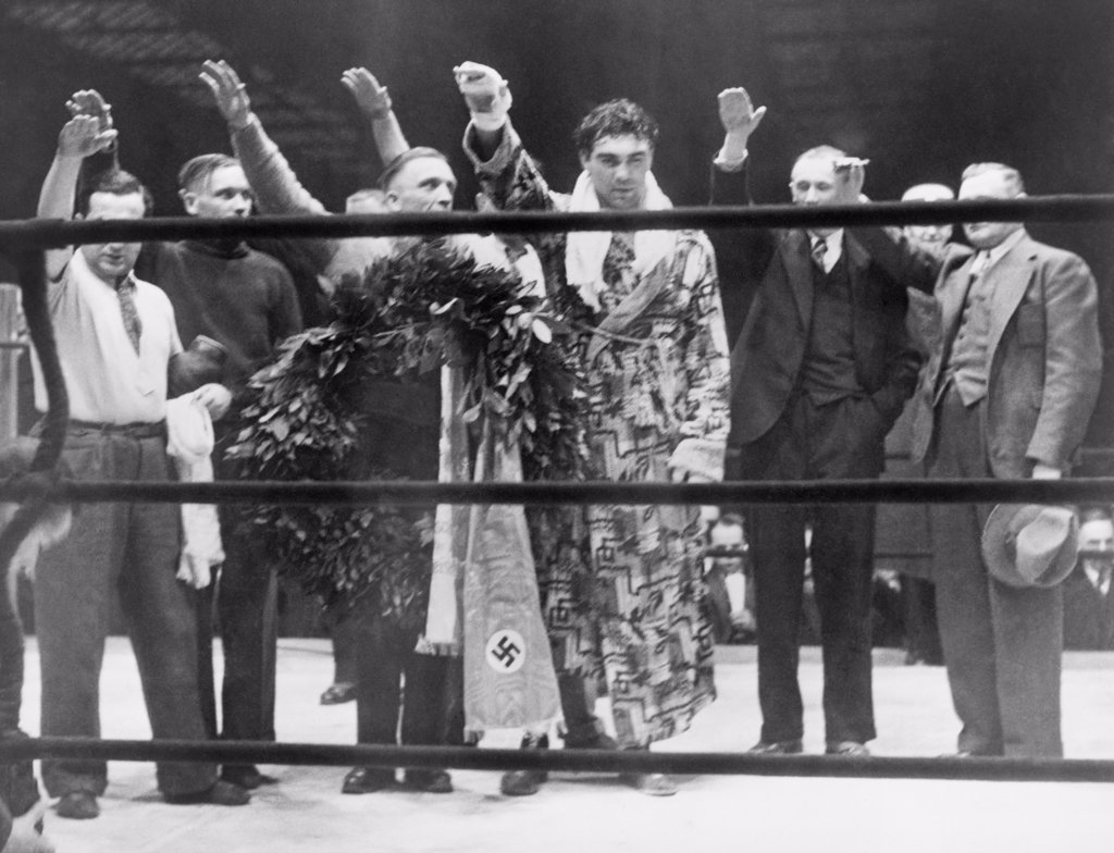 Max Schmeling, with attendants, giving the Nazi salute after his victory over Steve Hamas in Hamburg, Germany, March 10, 1935. : Stock Photo