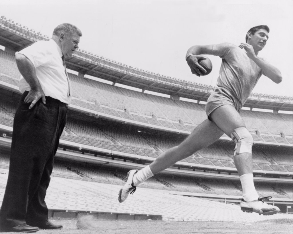 Stock Photo: 4048-5800 Joe Namath (b. 1943), quarterback with the New York Jets, running during light workout to test his injured knee, as coach Weeb Eubank observes. After his football career, Namath had knee replacement surgery. 1965.
