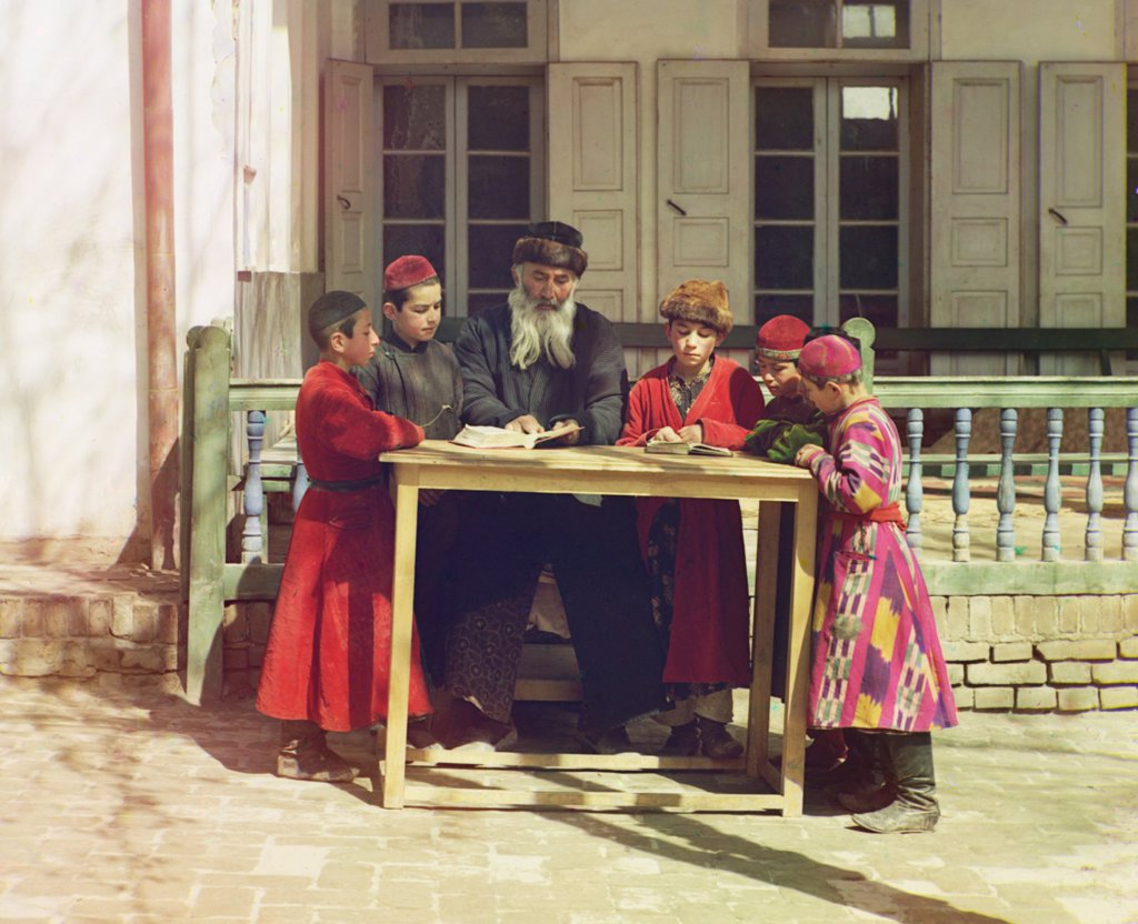 Group of Jewish boys with their teacher in Samarkand, ca. 1910. Samarkand's Jews lived under Muslim rule until the late 18th century, when Sephardic Moroccan Rabbi, Maghribi, arrived and began a revival Jewish religious life. Russia annexed the region in 1868 and built the Trans-Caspian railroad, ending their isolation from Europe. 1910 color photograph by Sergei Prokudin-Gorskii. : Stock Photo