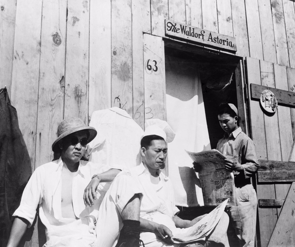 Stock Photo: 4048-6389 Japanese American men from Seattle, Washington sit outside a barracks during their four month stay at Puyallup Assembly Center in 1942. The Relocation Authority named the temporary internment facility, 'Camp Harmony.' The internees in turn named their barracks the 'The Waldorf Astoria.'