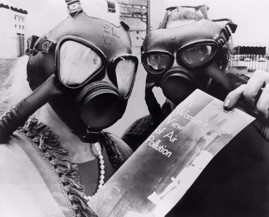 Stock Photo: 4048-6945 Mrs. Margaret Klein and Mrs. Marvin Blumenfeld, wearing gas masks, as they pass out a health bulletin, A WOMANS VIEW OF AIR POLLUTION at the Kiel Auditorium in St. Louis. 1966