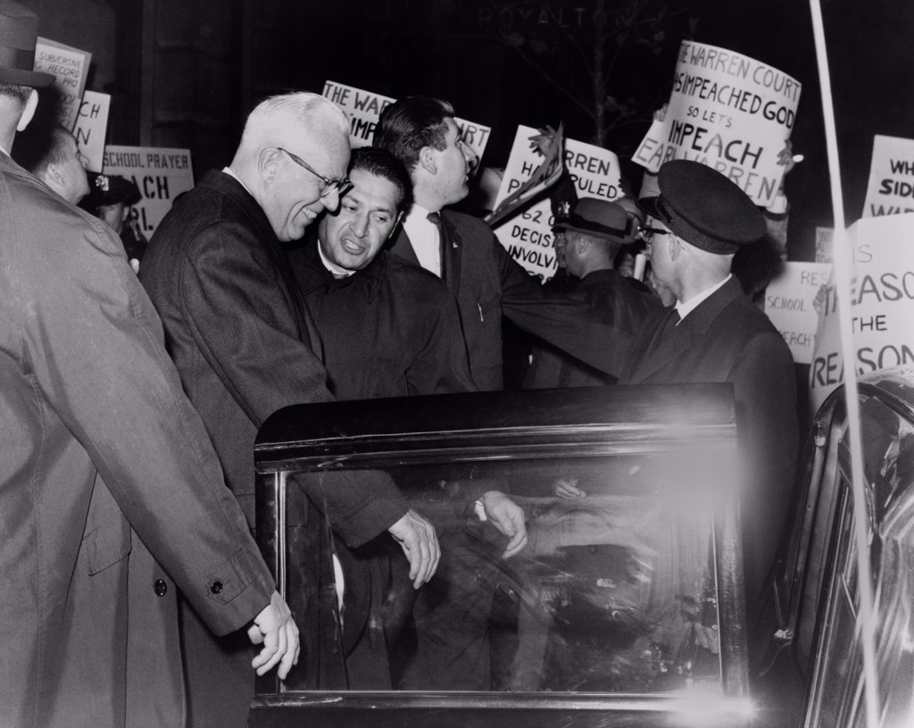 Chief Justice Earl Warren is escorted through crowd of protestors carrying placards attacking the Supreme Court's 1963 ruling (Abington School District v. Schempp) to prohibit prayer in U.S. public schools. : Stock Photo