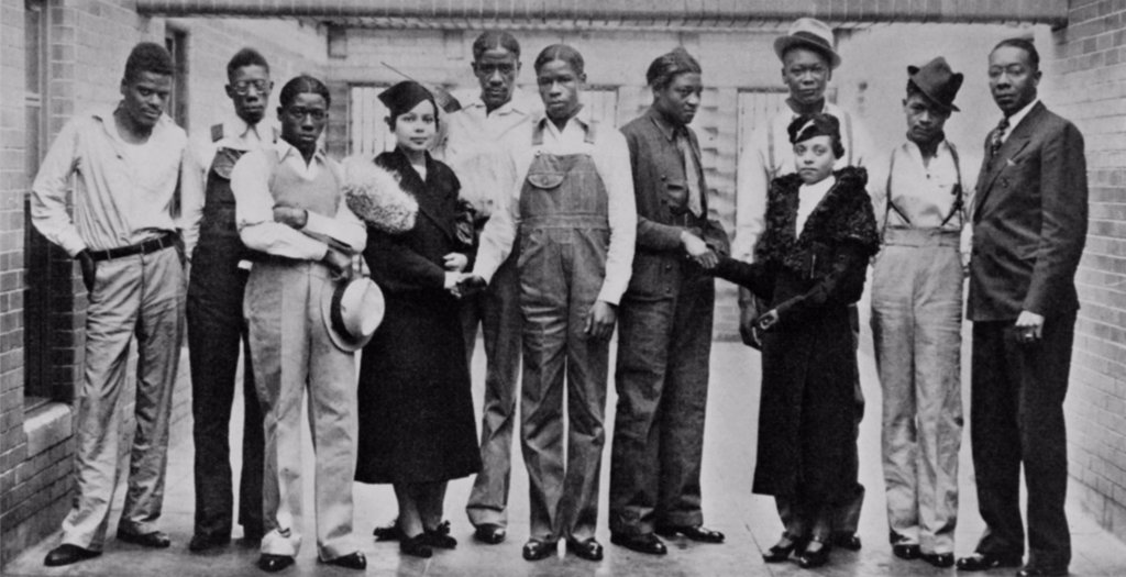 Stock Photo: 4048-7027 Juanita E. Jackson of the NAACP visiting Scottsboro boys, in Jefferson County Jail in Birmingham, Alabama, on Nov 20, 1936.  Left to right: Ozie Powell, Olen Montgomery, Willie Robinson, Miss Jackson, Charlie Weems, Clarence Norris, Haywood Patterson, Miss Laura Kellum of the Birmingham NAACP youth council, Andy Wright, Eugene Williams, Dr. E.W. Taggart, Pres. of the Birmingham NAACP.  Roy Wright, brother of Andy, refused to have his picture taken.