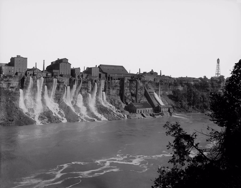 A cluster of factories built on and into the walls of the Niagara River Gorge. Water diverted from above the great Niagara Falls flows from the factories power generation plants. Ca. 1895. : Stock Photo