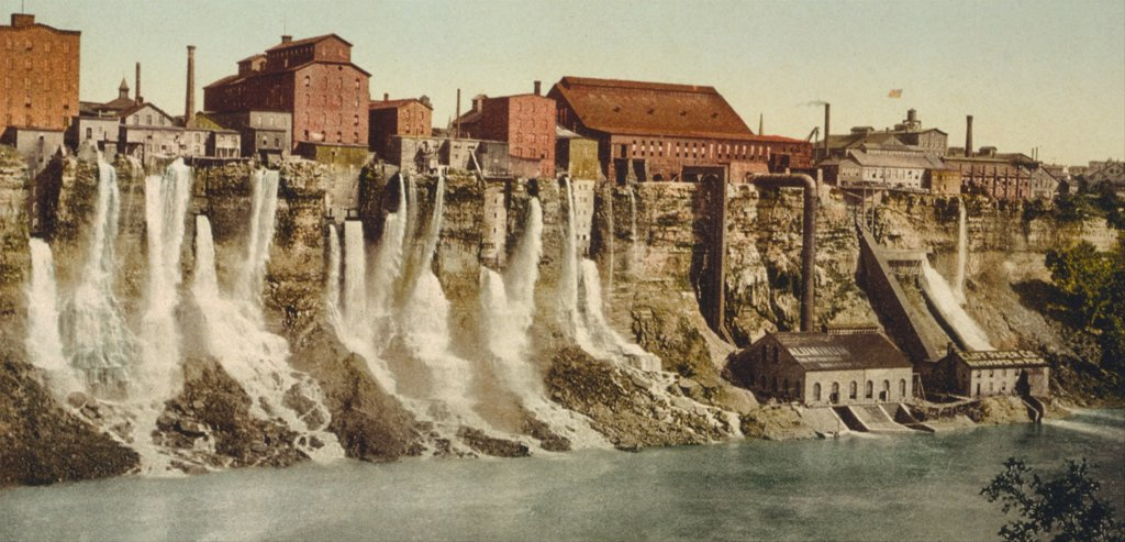 Stock Photo: 4048-7047 A cluster of factories built on and into the walls of the Niagara River Gorge. Water diverted from above the great Niagara Falls flows from the factories power generation plants. Ca. 1895.
