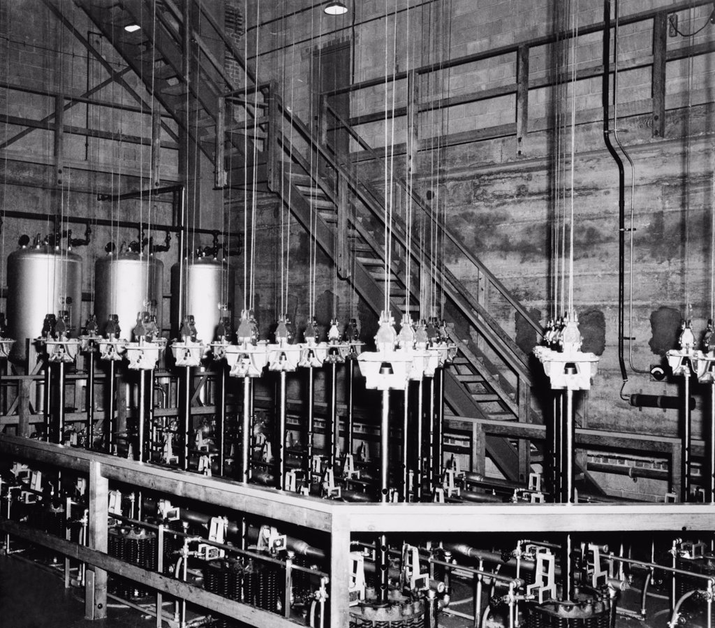 The vertical safety rods and the cables that support them at the top of the atomic pile of a reactor at the Manhattan Project Hanford site. The four silvered-colored drums in the background contained boron solution, part of an emergency shutdown system should the rods be blocked by an earthquake. February 1945. : Stock Photo