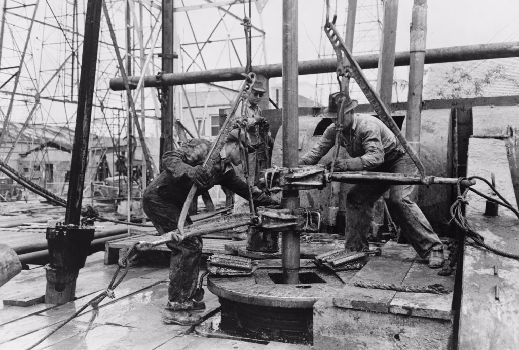 Stock Photo: 4048-7062 Oil rig workers, called roughnecks, at work, loosening sections of pipe on an drilling platform, Kilgore, Texas. 1939 Photo by Russell Lee.