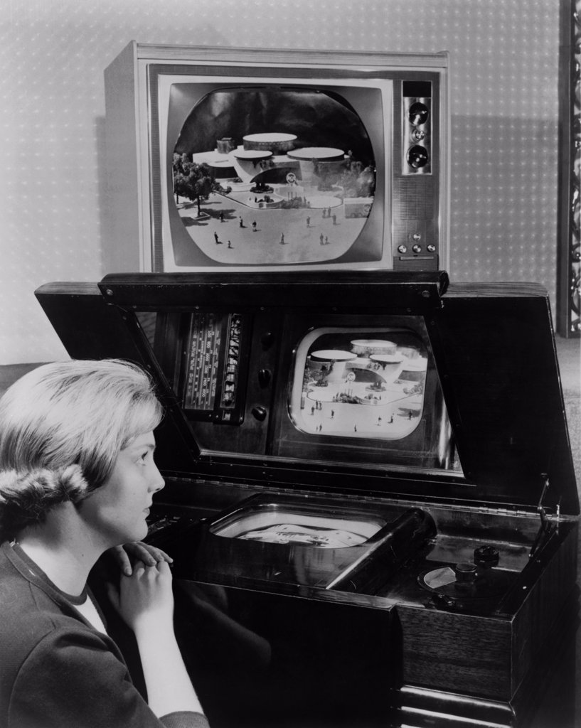 Woman looking at two television sets. One, similar to a set demonstrated at the 1939 New York World's fair, has a small screen incased horizontally in a large wooden cabinet and is viewed from a reflective mirror. The other, now displayed 25 years later at the 1964 New York World's fair, is a large screened color television. : Stock Photo