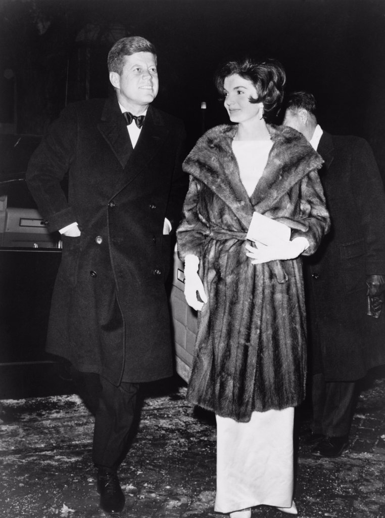 Stock Photo: 4048-7229 President and Mrs. Kennedy en route to a private party on March 7, 1961. On the cold winter night, Jacqueline Kennedy wears a mink coat.