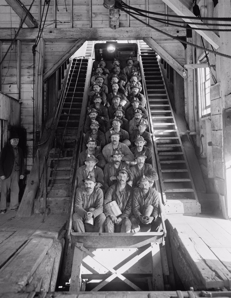 Stock Photo: 4048-7388 Miners in an open tram at the Calumet and Hecla Mining Company, one of the largest and most profitable copper mines in American in the late 19th and early 20th century, employing 5000 people. The mining superintendents were traditionally Cornishmen; the workers were Finns, Poles, Italians, Irish, and other immigrant nationalities. 1906.