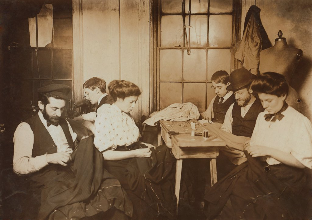 Garment workers sewing by hand in a small New York City sweatshop in1908. Photo by Lewis Hine. : Stock Photo