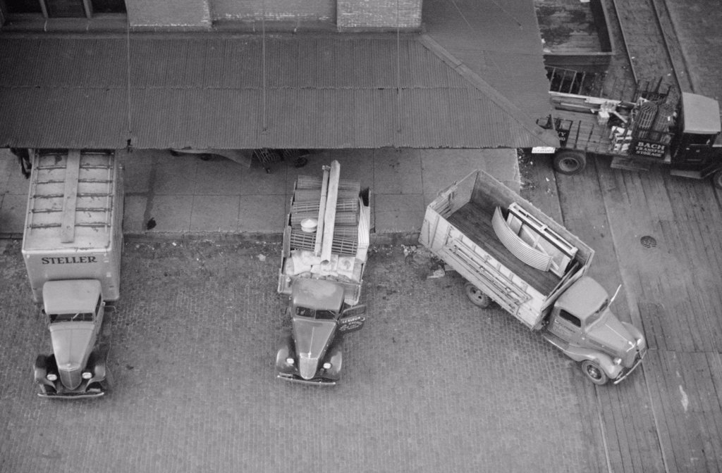Stock Photo: 4048-7610 Overhead view of trucks loading at farm implement warehouse, Minneapolis, Minnesota, 1939.