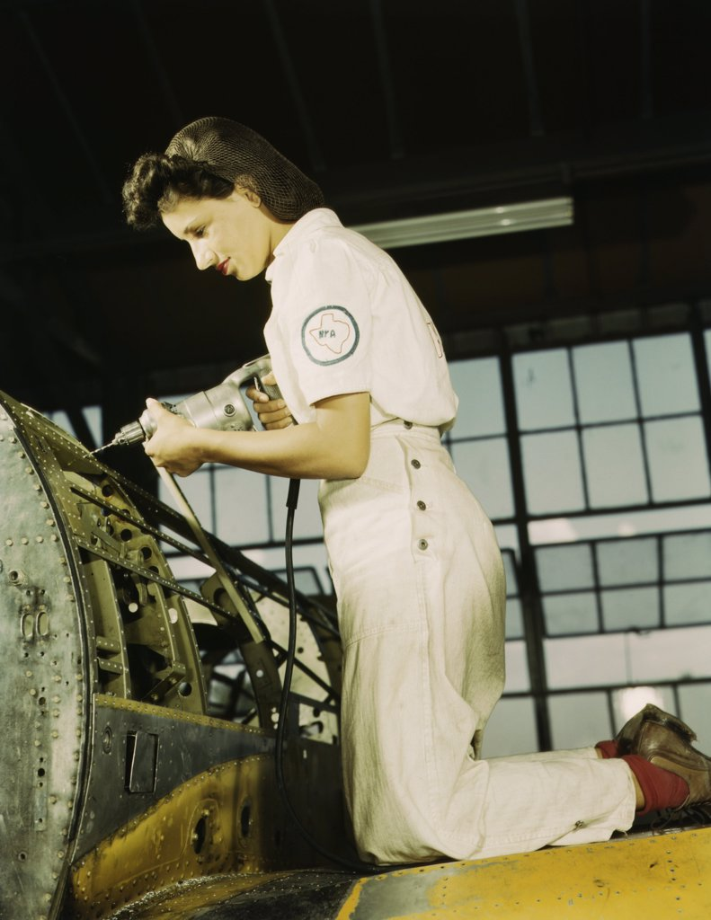 Stock Photo: 4048-7627 Defense worker riveting as part of her training to become a mechanic at the Naval Air Base, in Corpus Christi, Texas. August 1942.