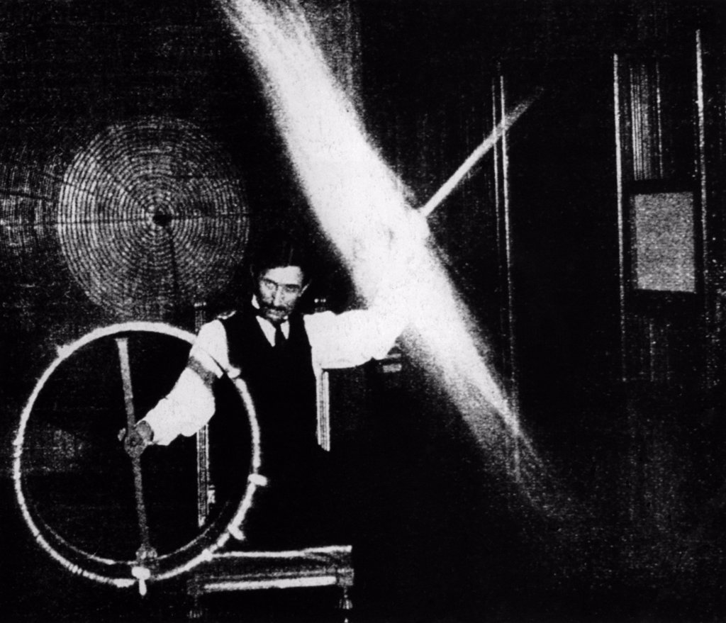 Nikola Tesla 1856-1943 conducted spectacular demonstrations of electricity. This image published in ELECTRICAL REVIEW in 1899 was accompanied by with this caption The operator's body in this experiment is charged to a high potential by means of a coil responsive to the waves transmitted to it from a distant oscillator. : Stock Photo
