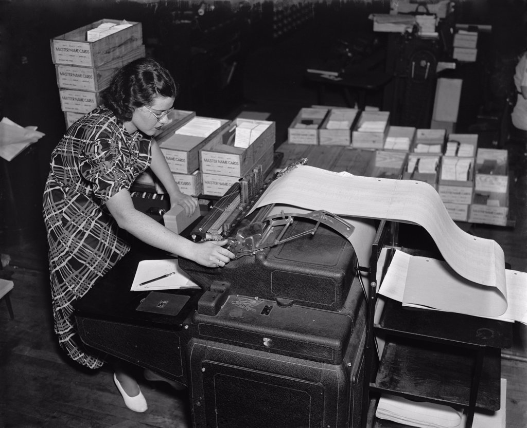 The new Social Security Administration was challenged with handling an unprecedented amount of information to track citizens' wage records and taxes paid. A government worker uses a state of the art mechanical tabulator to print a list Social Security account numbers. Ca. 1937. : Stock Photo