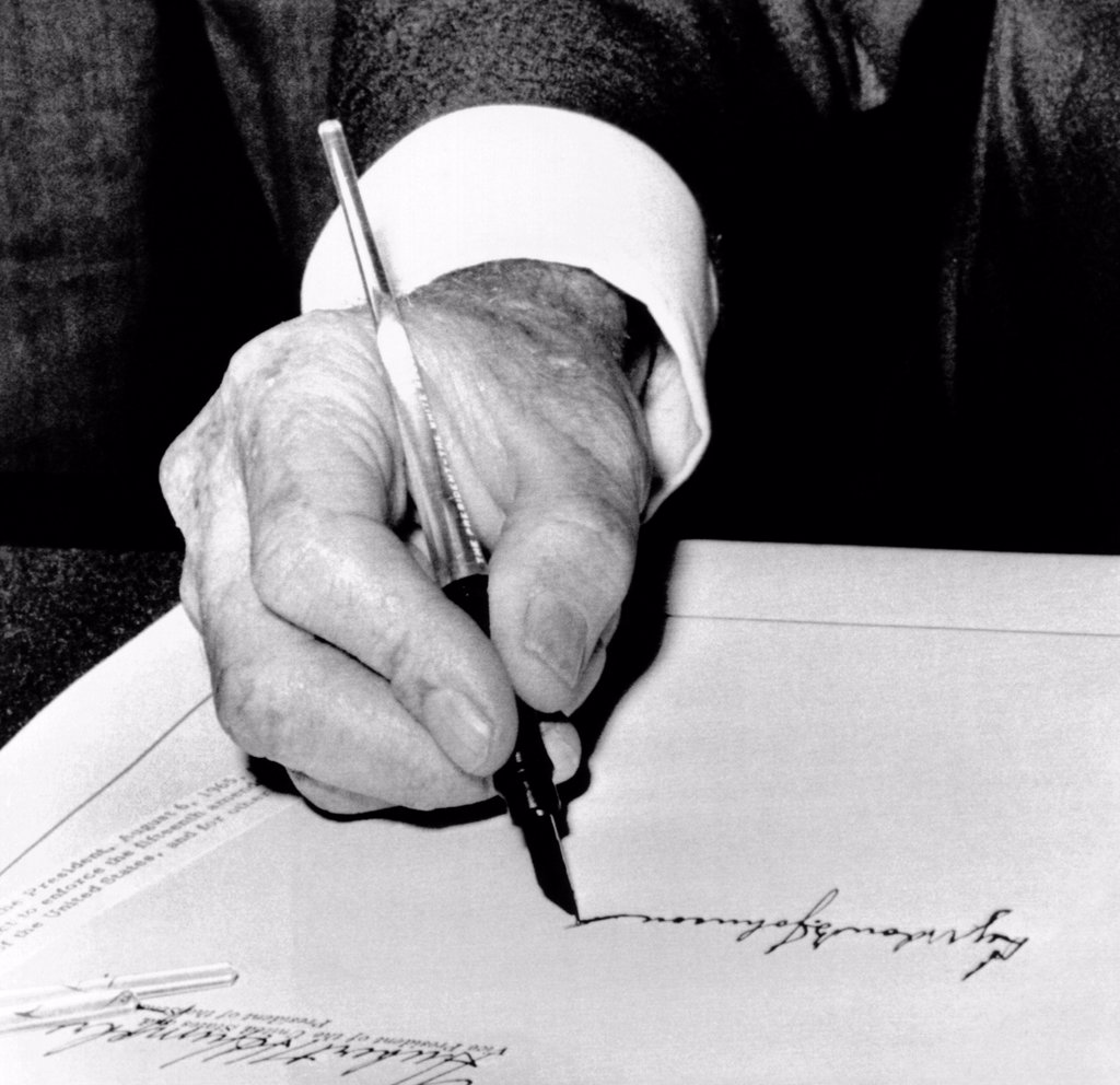 Stock Photo: 4048-8390 President Lyndon Johnson signing the 1965 Civil Rights Bill, also known as the Voting Rights Act. The law came seven months after Martin Luther King's Selma, Alabama campaign, which pressured Congress to pass the legislation. Aug. 6, 1965.
