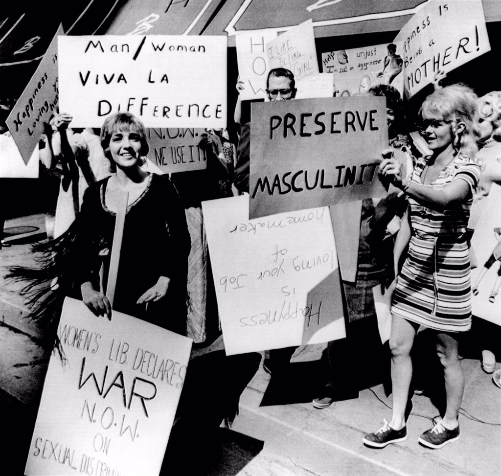 Stock Photo: 4048-8392 Anti-Women's Liberation protesters. They counter demonstrate with signs reading 'Viva la Difference', 'Preserve Masculinity', 'I like being a girl' and 'Happiness is being a mother.' A solitary feminist holds a sign, 'Women's liberation declares war now on sexual discrimination.' Aug. 26, 1970.