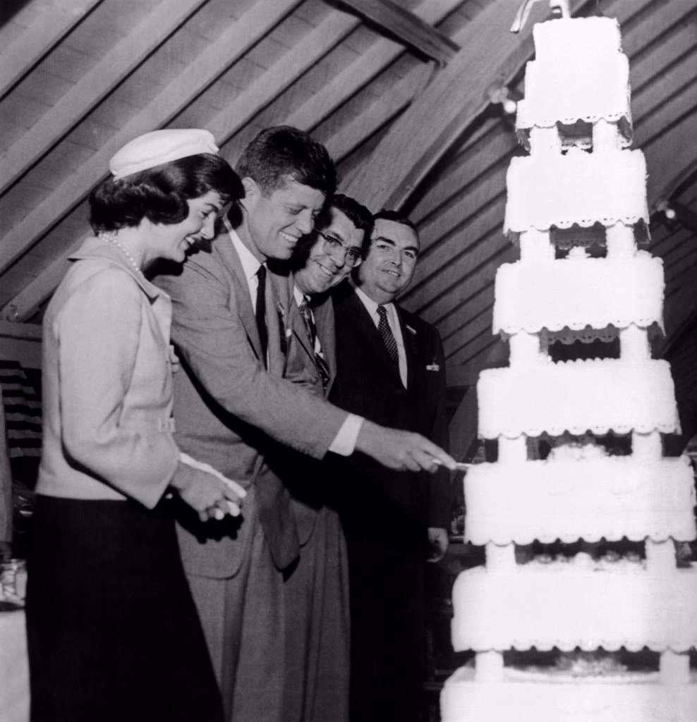 Senator John Kennedy cutting an multi-tier cake on his 39th birthday. He was honored with a testimonial dinner given by the cities of New Bedford and Fall River. L-R: Jacqueline Kennedy, Sen. Kennedy, Mayor Francis Lawler of New Bedford, Mayor John Kane of Fall River. May 29, 1956. : Stock Photo