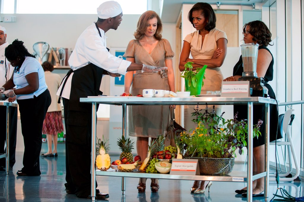 First Lady Michelle Obama and Valérie Trierweiler of France, center, watch a student cooking demonstration at the Gary Comer Youth Center in Chicago, Ill., May 20, 2012. : Stock Photo