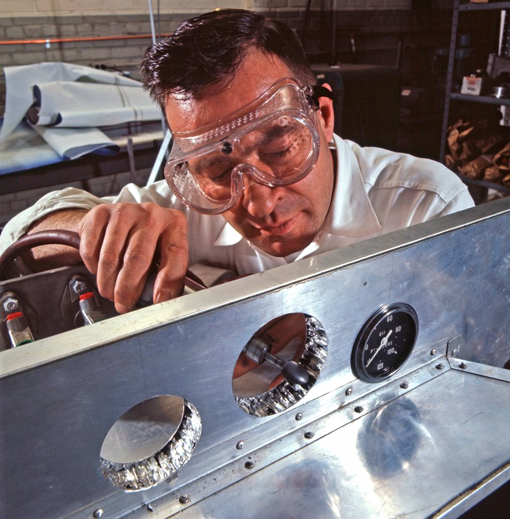 Ford engineer adjusts holes for dashboard instruments on a racing-car chassis made of honeycomb aluminum, a material full of air and resistant to metal fatique. Ford Motor Company, Dearborn Michigan, 1966. Photo: John G. Zimmerman Archive/Courtesy Everett Collection : Stock Photo
