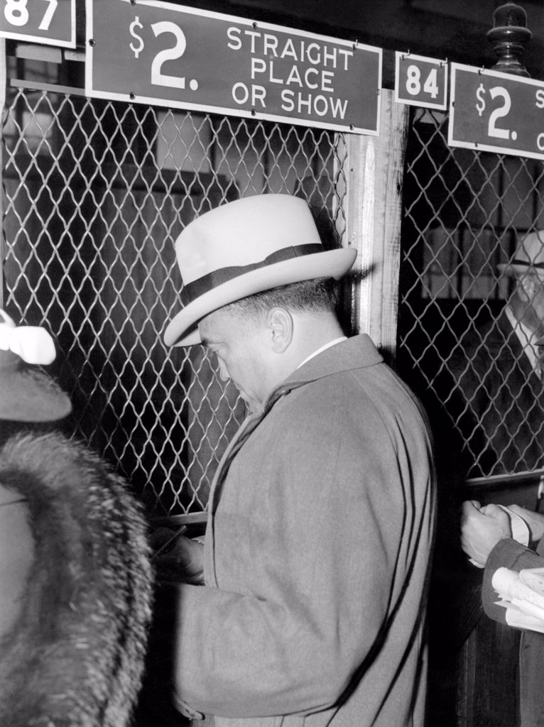 J. Edgar Hoover placing a bet at the two dollar window. It was opening day at Bowie race track, Maryland, April 1, 1938. : Stock Photo
