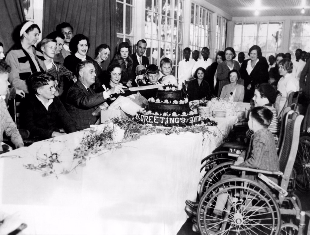 President-elect Franklin Roosevelt celebrating his 51st birthday. FDR cuts his birthday cake at the sanitarium for polio victims at Warm Springs, Georgia. Eleanor stands behind him on left. Jan. 30, 1933. : Stock Photo