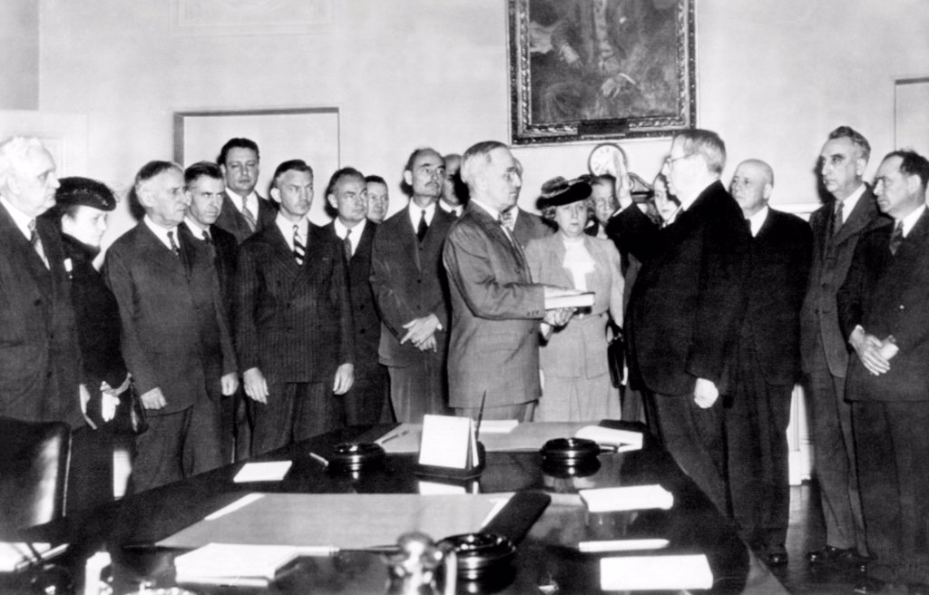 Vice President Harry Truman took the oath of office in White House Cabinet Room after Franklin Roosevelt's death. L-R: First man unidentified, Perkins, Stimson, Wallace, Krug, Forrestal, Wickard, Biddle, Truman, Mrs. Truman, Ickes (just behind Mrs. Truman), Margaret Truman, Chief Justice Stone, Sam Rayburn, Vinson, Joe Martin. April 12, 1945. : Stock Photo