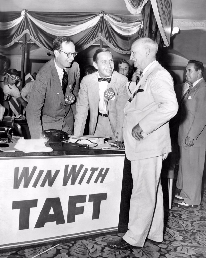 Stock Photo: 4048-8873 Senator Robert Taft's two sons promote their father's GOP Presidential nomination. At Taft headquarters in the Conrad Hilton hotel, William Howard Taft, 36, and Lloyd Taft, 29 chat with Delegate Myers Y. Cooper, former governor of Ohio. July 5, 1952.