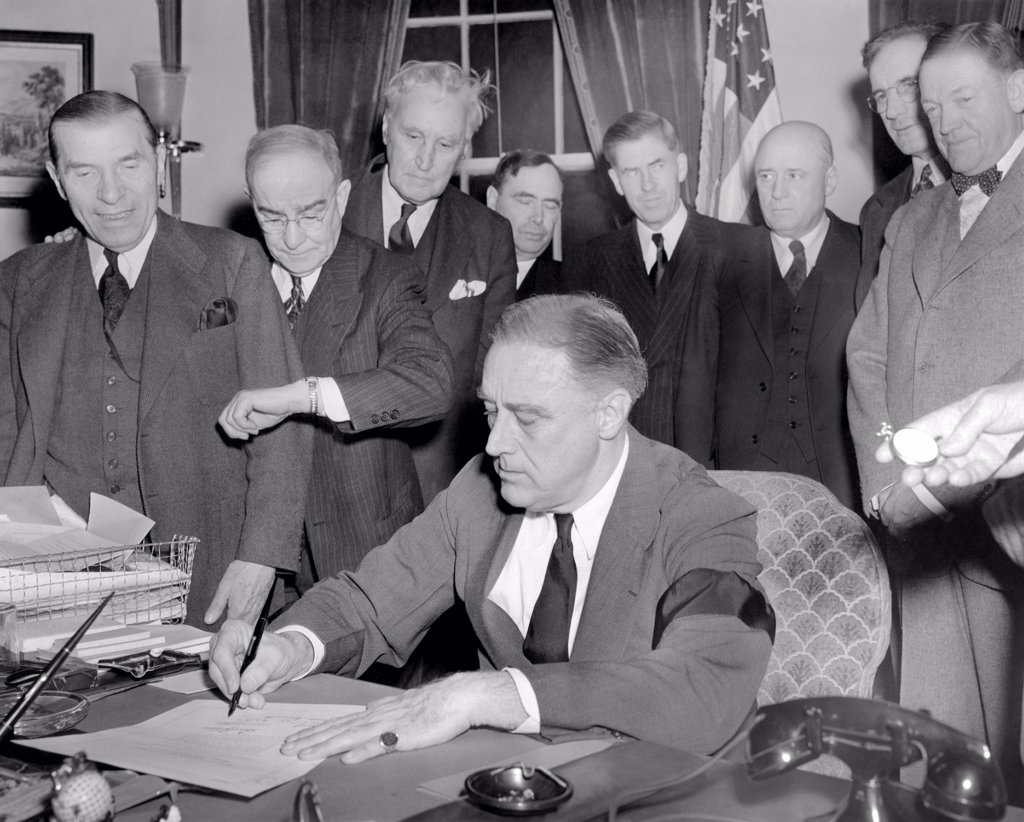 President Franklin D. Roosevelt signs the joint congressional resolution declaring war with Japan at 4:10 PM, Dec. 8, 1941. Standing L-R: Rep. Sol Bloom, Luther Johnson, timing the signing, Charles Eaton , Joseph Martin, Vice President Henry Wallace, Speaker Sam Rayburn, John McCormack, Massachusetts, and Senator Charles McNary. FDR wears a black arm in mourning for his recently deceased mother, Sara Delano Roosevelt. : Stock Photo