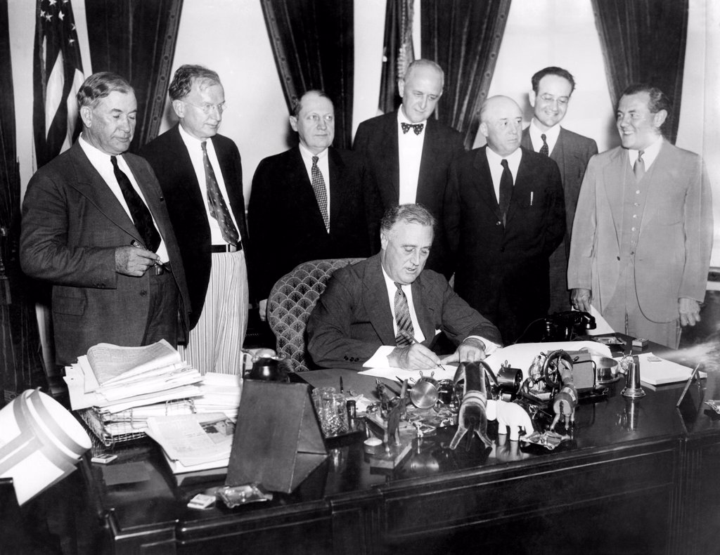 President Franklin Roosevelt, signs the Public Utility Holding Company Act of 1935 (Wheeler-Rayburn Act). It imposed consumer protection regulations on public utilities and was bitterly fought by the industry. Standing L-R: Sen. Alben Barkley, Sen. Burton Wheeler, Sen. Fred H. Brown, Dozier Du Vane, Solicitor, Federal Power Commission, Rep. Sam Rayburn, Benjamin Cohen, Attorney, and Thomas Corcoran, attorney. Aug. 26, 1935. : Stock Photo