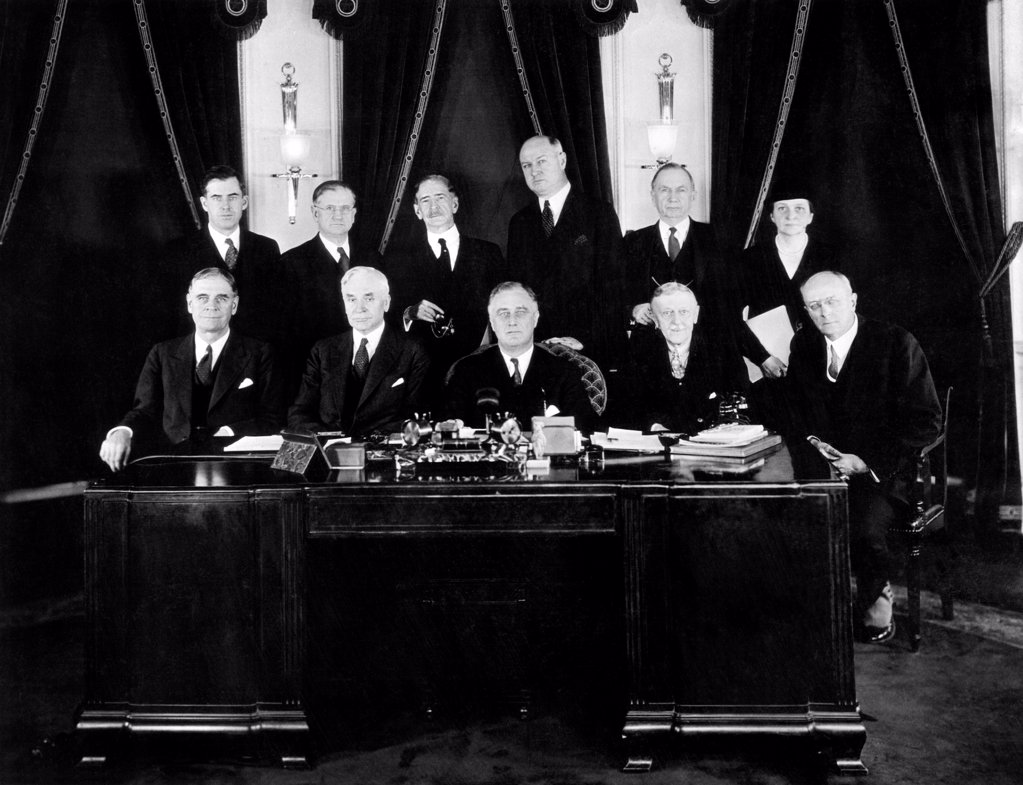 Stock Photo: 4048-9058 Dec. 21, 1933. Franklin Roosevelt with his Cabinet. At head of table is FDR seated at his desk in the White House. L-R seated: George Dern, (War), Cordell Hull (State), FDR, William Woodin (Treasury) and Homer Cummings (Attorney Gen.). L-R standing: Henry Wallace (Agriculture), Harold Ickes (Interior), Claude A.Swanson, (Navy Secy), James Farley (Postmaster), Daniel Roper (Commerce), Francis Perkins (Labor). Dec. 21, 1933.