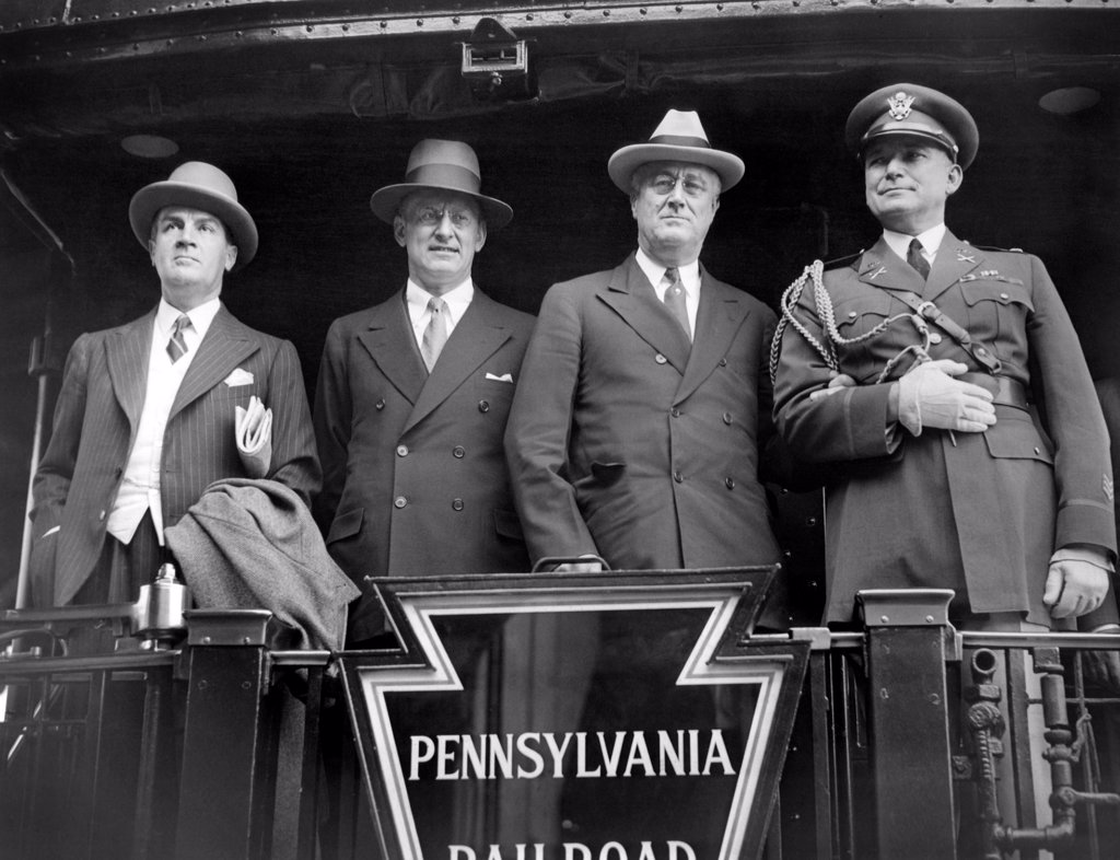 Stock Photo: 4048-9073 President Franklin Roosevelt observes Memorial Day. FDR posed for photographers on the back of his train to Gettysburg, where he will make a Memorial Day speech. L-R: Warren Robbins, American Minister to Canada, Henry Morgenthau Jr., Secy. Of the Treasury, President Roosevelt, and Colonel Edwin Watson, White House Military aide. April 30, 1934.