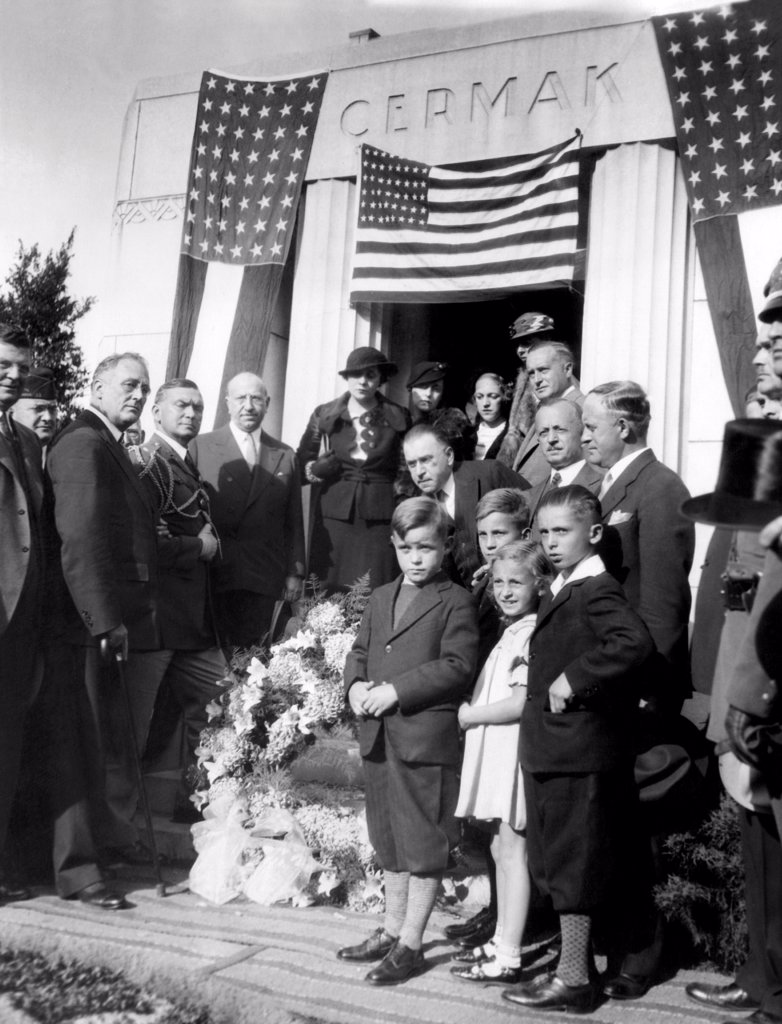 President Franklin Roosevelt at the grave of Chicago mayor, Anton Cermak. While standing next to President-elect FDR, on Feb. 15, 1933, Cermak was shot by Giuseppe Zangara and later died. L-R: Franklin Roosevelt, Col. Edwin Watson, Illinois Gov. Henry Horner, Eleanor Roosevelt, Friends and family of the slain mayor. Oct. 2, 1933. : Stock Photo