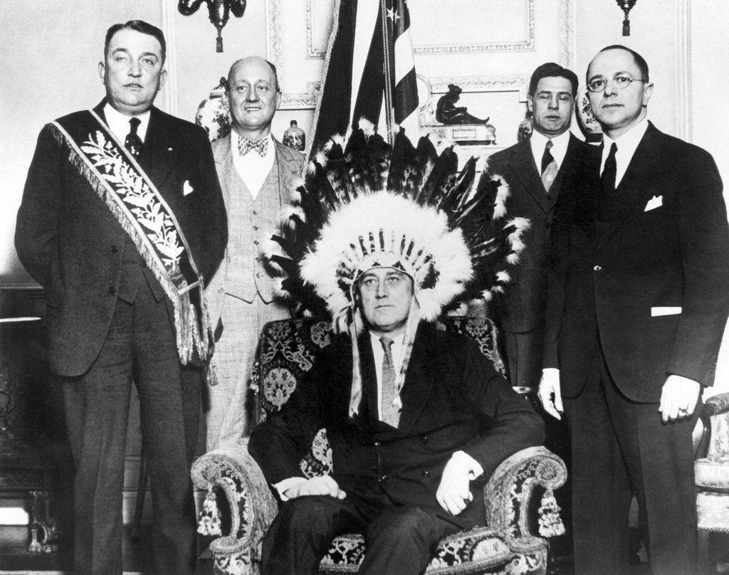 Governor Franklin Roosevelt made a member of the Fraternal Order of Red Men. The order was inspired by the Indian costumes worn by the patriots at the Boston Tea Party. Jan. 1930. L-R: Judge Harry Cathriell, national head of the Red Men, Gilbert Orrin Townsend, Gov. Roosevelt, Guernsey Cross, Governor's secretary, and Louis Butler. : Stock Photo