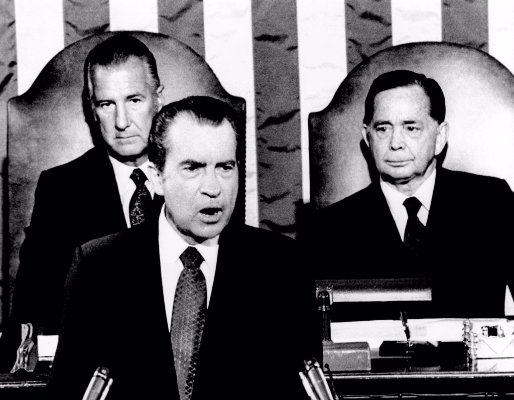 Stock Photo: 4048-9185 Addressing Congress, President Richard Nixon announces a 90-day wage-rent freeze to be started on August 15, 1971, would not be extended. Behind him are Vice Pres. Spiro Agnew (left) and House speaker Carl Albert. Sept. 9, 1971.