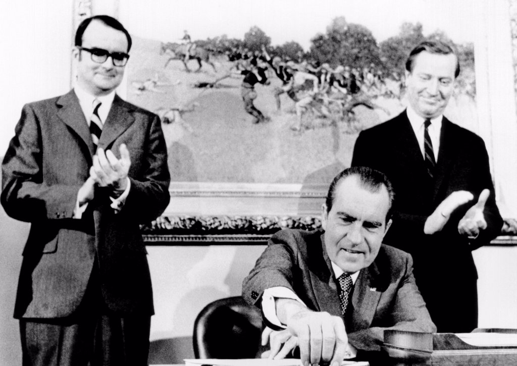 President Richard Nixon signs far reaching anti-pollution legislation. It will require the auto industry to produce virtually emission free cars by 1976. Applauding are William Ruckelshaus (left), head of the Environmental Protection Agency, and Russell Train, chairman of the Council on Environmental Quality. Dec. 31, 1970. : Stock Photo