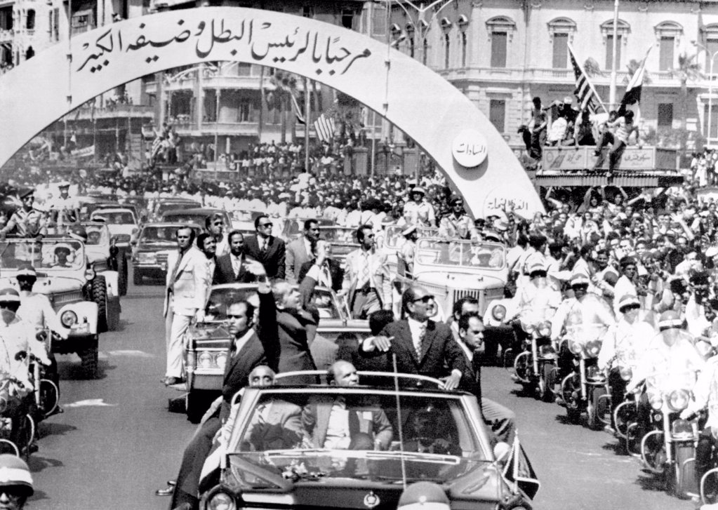 President Richard Nixon and President Sadat parade in Alexandria, Egypt. The arch reads in Arabic, 'Welcome Leader and his Great Guest.' June 13, 1974. : Stock Photo