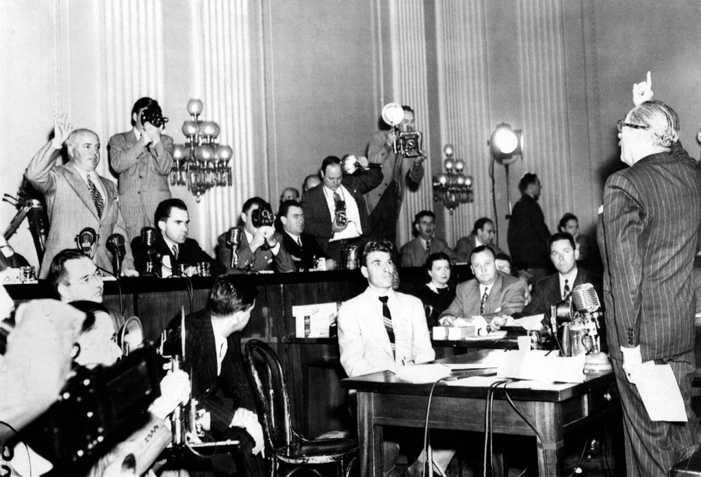 Stock Photo: 4048-9310 Screen actor Adolphe Menjou (right) is sworn in to testify before HUAC. Menjou was a active member of the 'Motion Picture Alliance for the Preservation of American Ideals', an anti-Communist group whose members included John Wayne and Barbara Stanwyck. At the HUAC table, (L-R): J. Parnel Thomas, Richard Nixon, a movie cameraman, and Richard Vail. Oct. 21, 1947.
