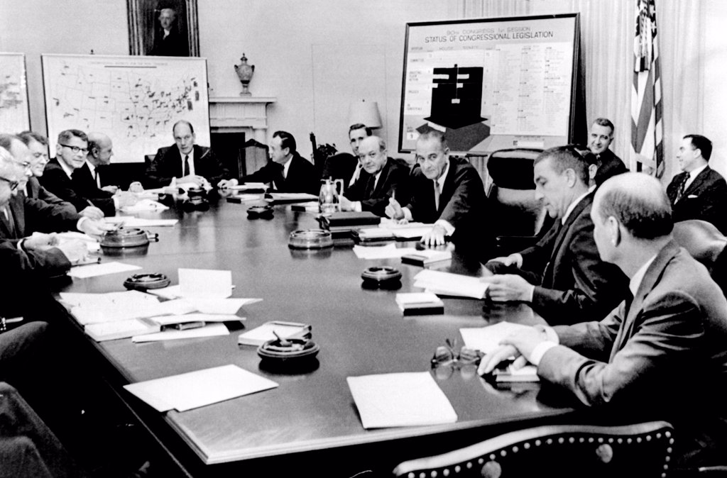 President Lyndon Johnson meets with his Cabinet. A chart lists the status of Congressional legislation. May 16, 1967. L-R: Arthur Goldberg, Gardner Ackley, Cyrus Vance, Orville Freeman, Robert Weaver, Alan Boyd, Herbert Holloman, Dean Rusk, President Johnson, Joseph Barr, hidden, Stewart Udall, Ralph Huitt. In background Henry Hall Wilson, and Joseph Califano. : Stock Photo