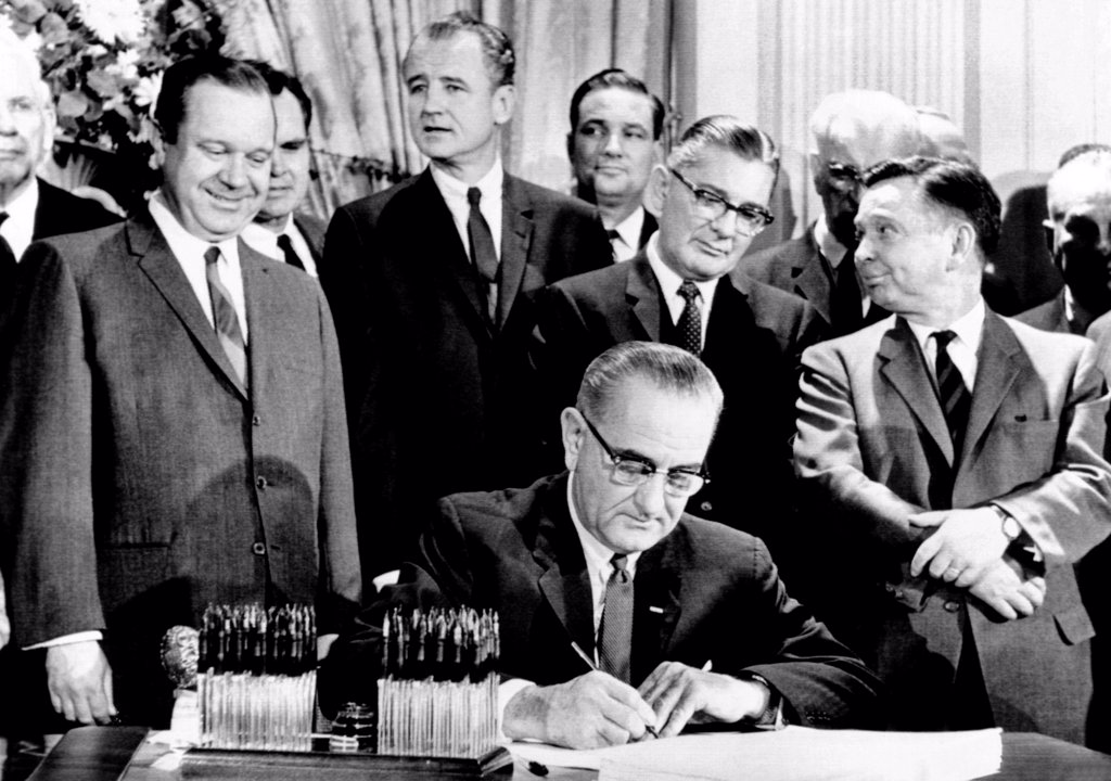 Stock Photo: 4048-9394 President Lyndon Johnson signs a $11.5 billion tax cut bill. Standing, L-R: Russell Long, Al Ullman, George Smathers, Pat Jennings, Wilbur Mills, John McCormack, Carl Albert. Feb. 26, 1964.