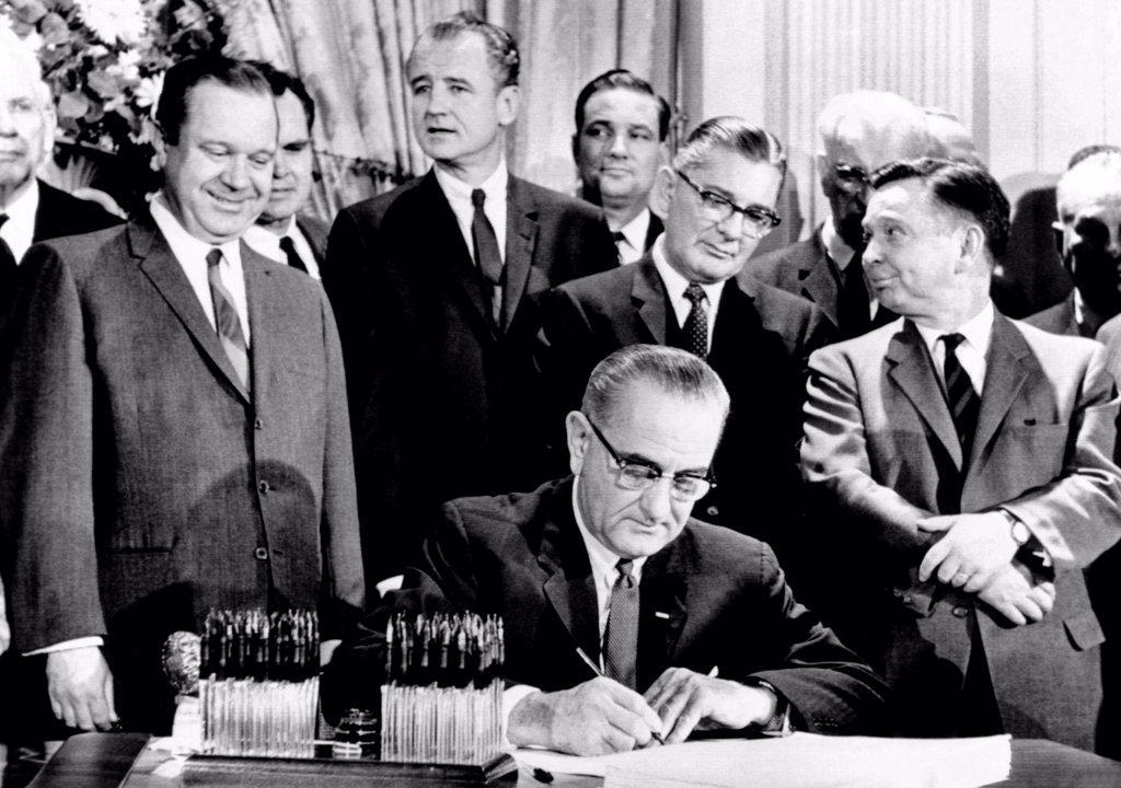 President Lyndon Johnson signs a $11.5 billion tax cut bill. Standing, L-R: Russell Long, Al Ullman, George Smathers, Pat Jennings, Wilbur Mills, John McCormack, Carl Albert. Feb. 26, 1964. : Stock Photo