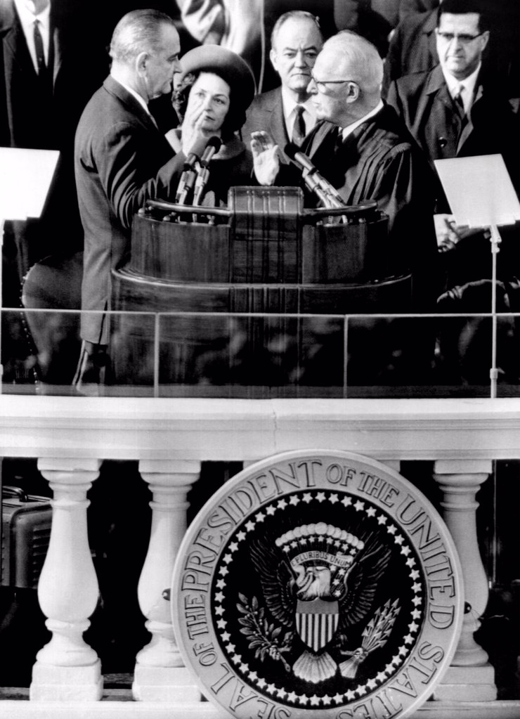 President Johnson takes the oath of office at his 1964 Inauguration. L-R: President and Mrs. Johnson, Vice President Hubert Humphrey, and Chief Justice Earl Warren. Jan. 20, 1964. : Stock Photo