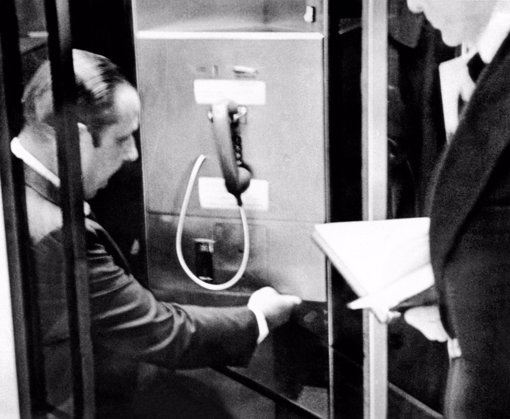 Stock Photo: 4048-9547 Anthony Ulasewicz, was a former New York City detective who worked as private investigator for the White House. Photo shows Ulasewicz taping a key to an airport public telephone to a locker containing money for Howard Hunt, one of the Watergate burglars. July 23, 1973.